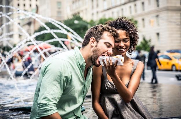 Coppie felici che mangiano i hot dog e che si divertono a new york city