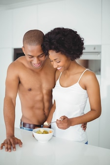 Coppie felici che mangiano insieme frutta nella cucina a casa