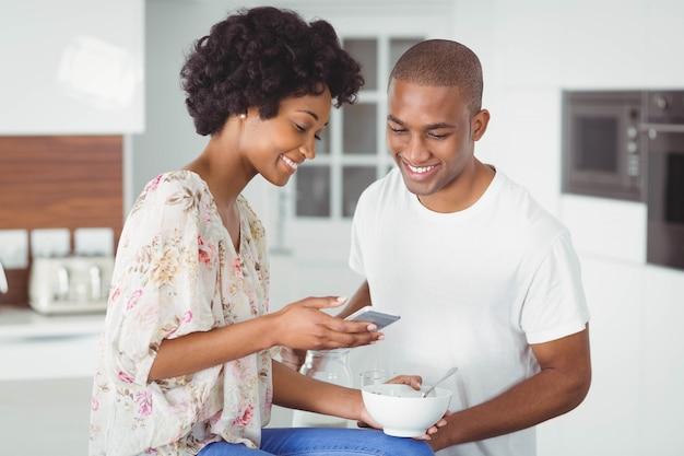 Coppie felici che mangiano prima colazione e che utilizzano smartphone nella cucina a casa