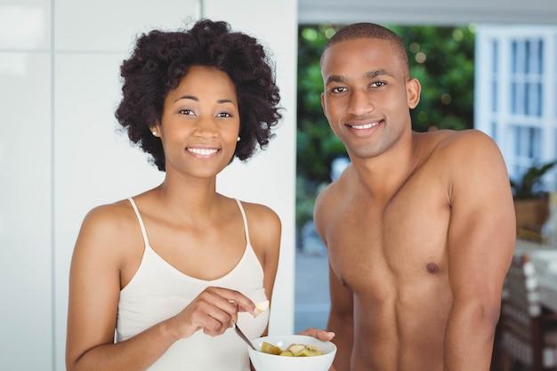 Coppie felici che mangiano prima colazione nella cucina a casa