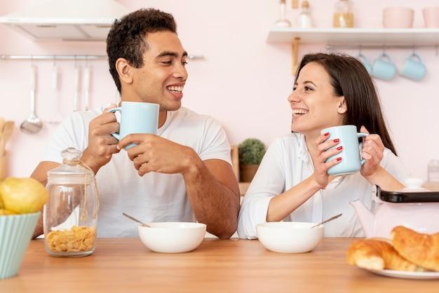 Coppie felici che mangiano prima colazione nella cucina