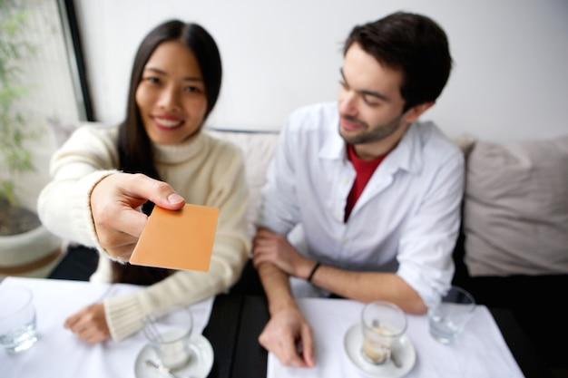 Coppie felici che pagano per il pasto con la carta al ristorante