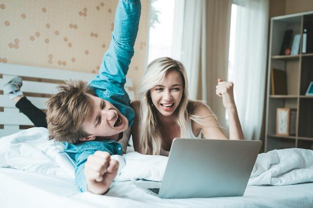Coppie felici che per mezzo del computer portatile sul letto