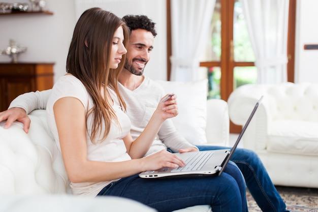 Coppie felici che per mezzo di un computer portatile sul sofà