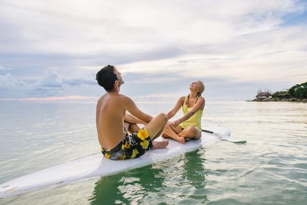 Coppie felici che praticano il surfing insieme sul bordo di pagaia al tramonto