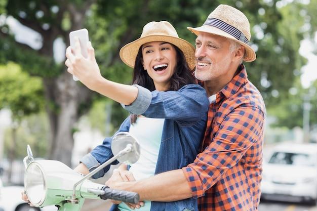 Coppie felici che prendono selfie sul ciclomotore