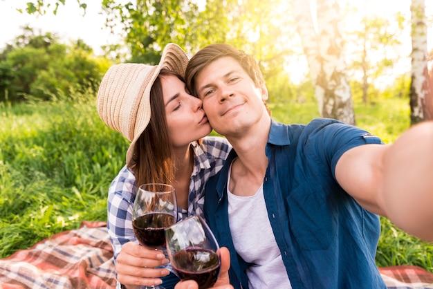 Coppie felici che prendono selfie sul picnic