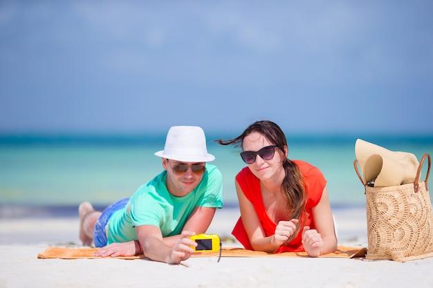 Coppie felici che prendono una foto di auto su una spiaggia in vacanza