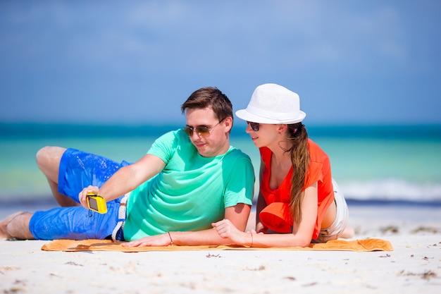 Coppie felici che prendono una foto su una spiaggia in vacanza