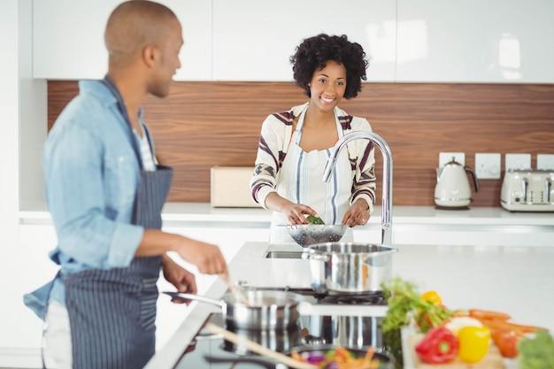 Coppie felici che preparano pasto in cucina