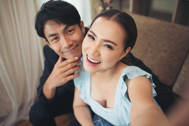 Coppie felici che ridono e che prendono un selfie con il telefono che si siede su uno strato a casa