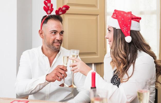 Coppie felici che risuonano i vetri del champagne alla tavola festiva