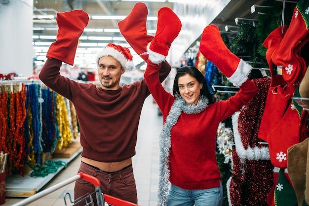 Coppie felici che scelgono i calzini di natale per i regali in supermercato