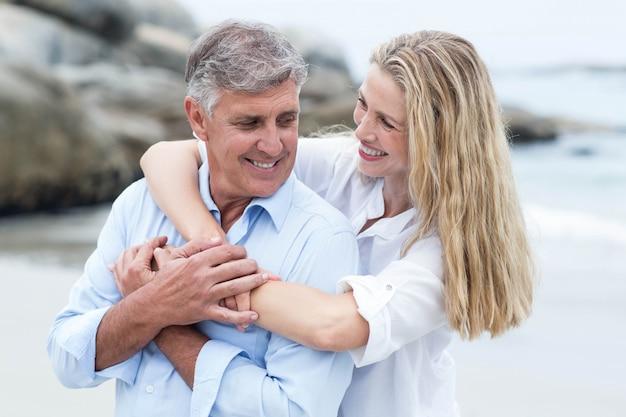 Coppie felici che si abbracciano dal mare