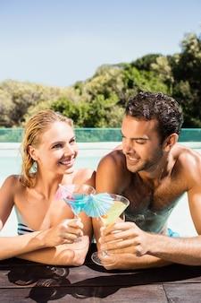 Coppie felici che si appoggiano sul bordo dello stagno e che tostano con i cocktail in un giorno soleggiato