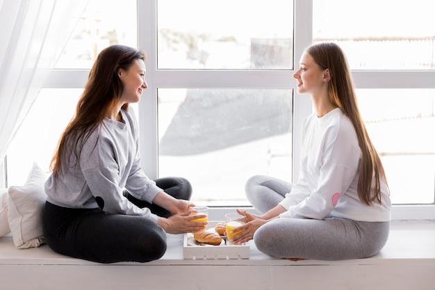 Coppie felici che si siedono alla finestra con la prima colazione