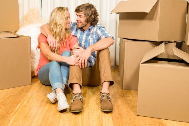 Coppie felici che si siedono sul pavimento nella loro nuova casa