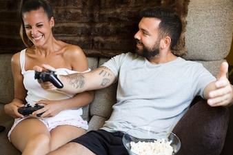 Coppie felici che si siedono sul sofà che guarda video gioco