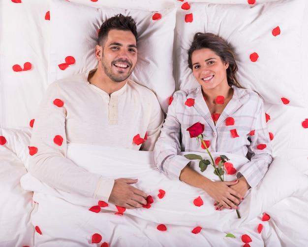 Coppie felici che si trovano a letto con i petali di rosa