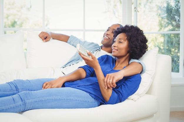 Coppie felici che si trovano sul sofà che tiene a distanza nel salone