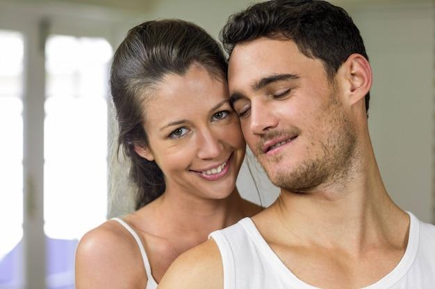 Coppie felici che sorridono alla macchina fotografica in cucina