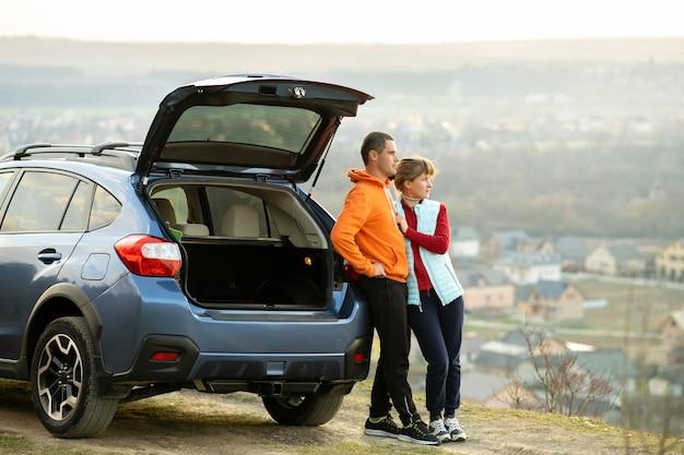 Coppie felici che stanno insieme vicino ad un'automobile