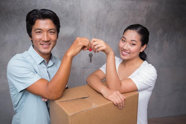 Coppie felici che tengono la chiave della casa e che si appoggia sulla scatola commovente