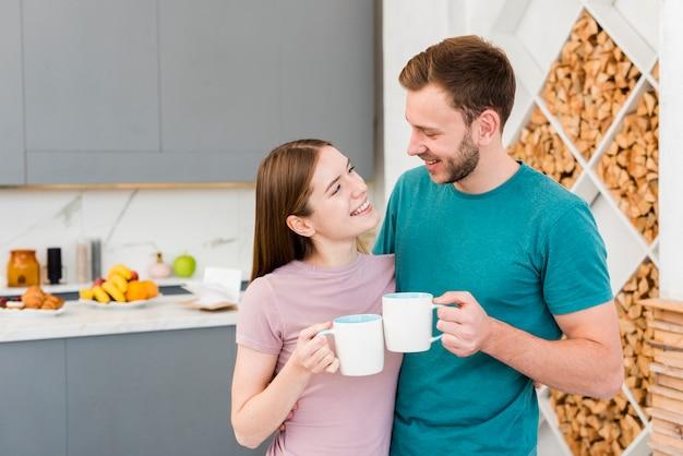 Coppie felici che tengono le tazze nella cucina