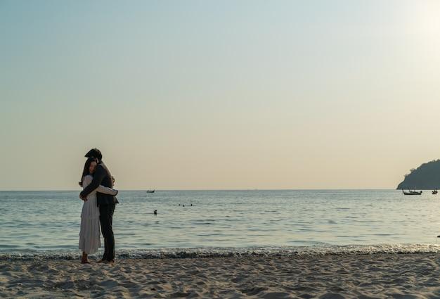 Coppie felici che vanno in viaggio di nozze sulla spiaggia di sabbia tropicale in estate