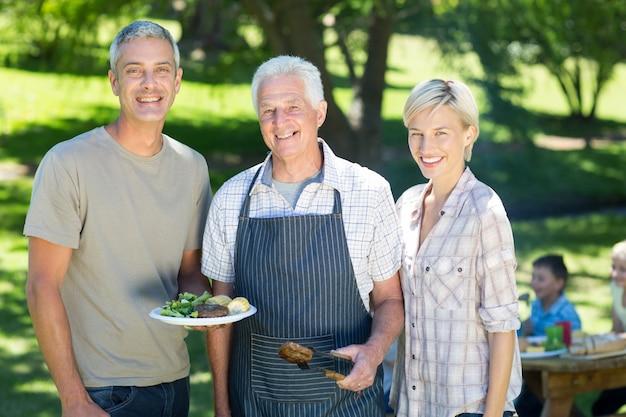 Coppie felici con il nonno che fa barbecue