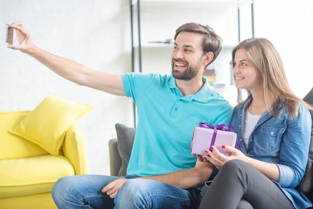 Coppie felici con il regalo del biglietto di s. valentino che prende selfie sullo smartphone
