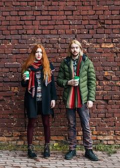 Coppie felici dei turisti in vestiti urbani caldi che stanno con le tazze eliminabili del caffè sul muro di mattoni