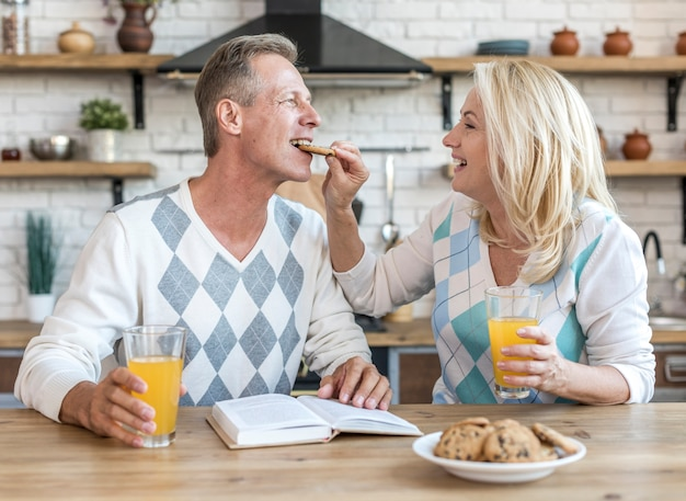 Coppie felici del colpo medio che mangiano prima colazione insieme