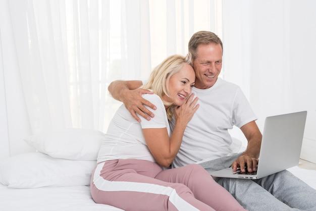 Coppie felici del colpo medio con il computer portatile nella camera da letto