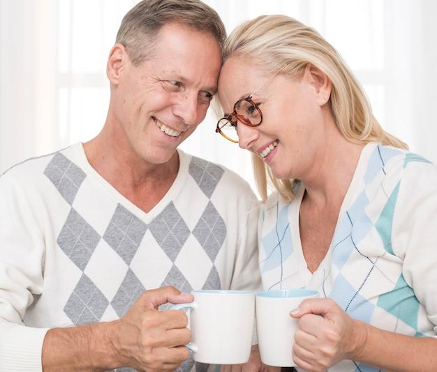 Coppie felici del colpo medio con le tazze che stanno insieme