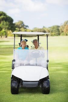 Coppie felici del giocatore di golf che si siedono in carrozzino di golf