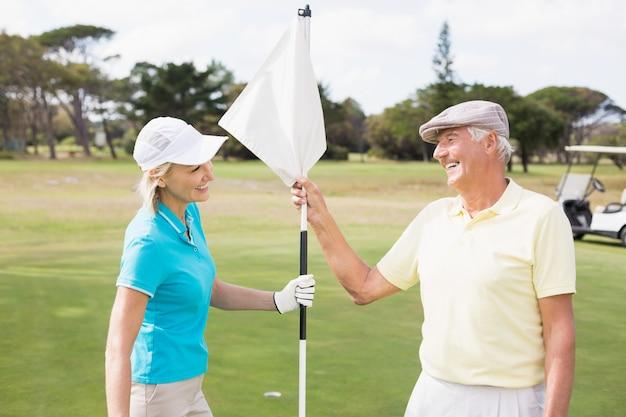 Coppie felici del giocatore di golf che tengono bandiera bianca
