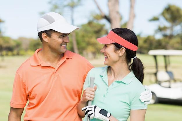 Coppie felici del giocatore di golf con il braccio intorno