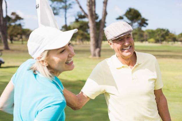 Coppie felici del giocatore di golf con la bandiera bianca