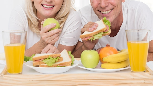 Coppie felici del primo piano che mangiano insieme