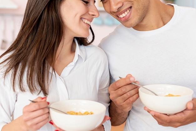 Coppie felici del primo piano con cereali e latte