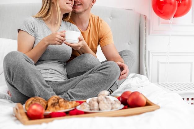 Coppie felici del primo piano con la prima colazione a letto