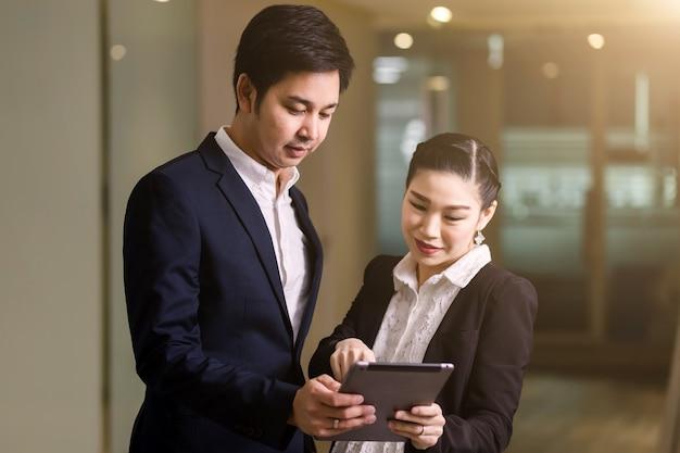 Coppie felici di affari con il tablet