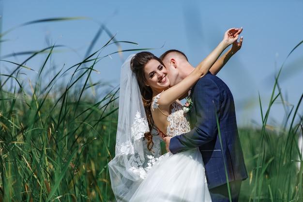Coppie felici di nozze che camminano sul ponte di legno. sposi emotivi che abbracciano delicatamente all'aperto.