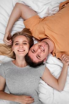 Coppie felici di vista superiore che si situano a letto