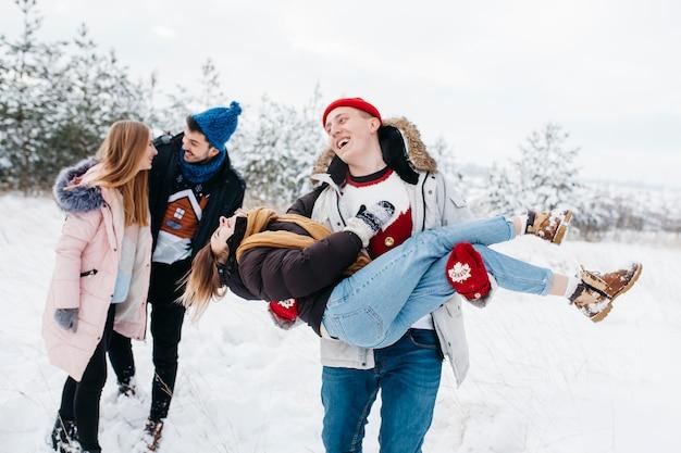 Coppie felici divertendosi nella foresta di inverno
