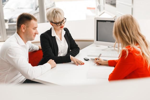Coppie felici e commerciante che firmano un documento in ufficio dopo l'affare