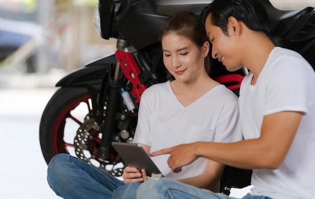 Coppie felici facendo uso della compressa digitale a casa con una motocicletta