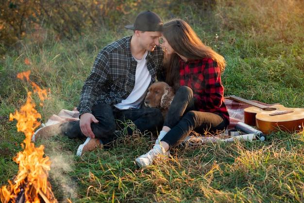 Coppie felici in abbigliamento casual con il loro cane divertente che si siede sul prato inglese nel parco di primavera.