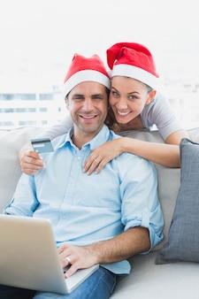 Coppie felici in cappelli della santa che acquistano online con il computer portatile